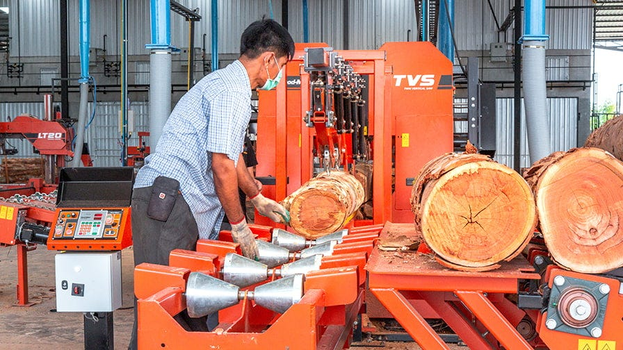 Manually turning logs on the infeed. Optional mechanized turning is available.